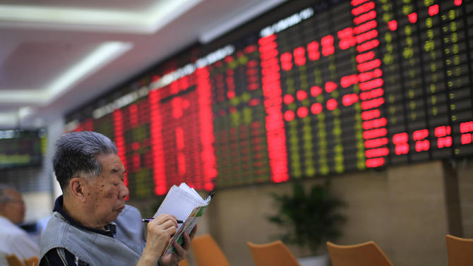 An investor keeps a memo as he sits in front of the stock price monitor at a private securities company in Shanghai, China, Tuesday, May 14, 2013. Asian stock markets were mixed Tuesday in a lukewarm reaction to data showing that U.S. consumers revved up their retail spending last month. (AP Photo/Eugene Hoshiko)