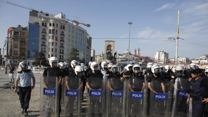 Riot policemen take their position during clashes in Taksim Square in Istanbul, Turkey, Tuesday, June 11, 2013. Hundreds of police in riot gear forced through barricades in Istanbul's central Taksim Square early Tuesday, pushing many of the protesters who had occupied the square for more than a week into a nearby park. (AP Photo/Kostas Tsironis)