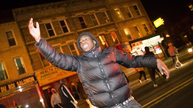 """A demonstrator signals to fellow marchers as they take to the street following a vigil held for Kimani """"Kiki"""" Gray in the East Flatbush neighborhood of New York's Brooklyn borough, Wednesday, March 13, 2013, in New York. According to the NYPD, the teen pointed a .38-caliber revolver at the plainclothes officers, who responded by shooting him to death. (AP Photo/John Minchillo)"""