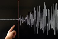 A scientist points to a seismograph of a major earthquake. An earthquake on Sunday hit a mountainous area of southwest China, killing at least two people and injuring around 100, according to the official Xinhua news agency