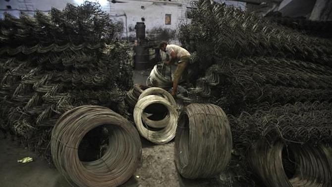 A labourer work inside an iron wire manufacturing factory on the outskirts of Jammu October 9, 2012.