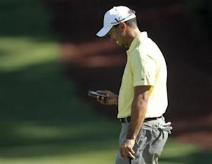 Woods looks at his iPhone after using it to take a picture of playing partner O'Meara on the 10th green, during a practice round for 2010 Masters golf tournament at Augusta National Golf Club