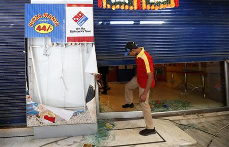 An employee enters the Dominos Pizza outlet after it was ransacked by the activists of RPI in a Mumbai suburb