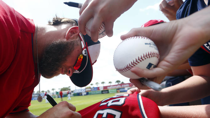 Washington Nationals right fielder Bryce Harper (34) signs autograph before the first inning of an exhibition spring training baseball game against the New York Mets Tuesday, March 31, 2015, in Viera , Fla. (AP Photo/John Bazemore)