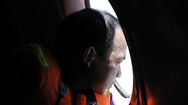 A man looks out a window during a search and rescue mission onboard an aircraft belong to the Vietnamese airforce off Vietnam's Tho Chu island