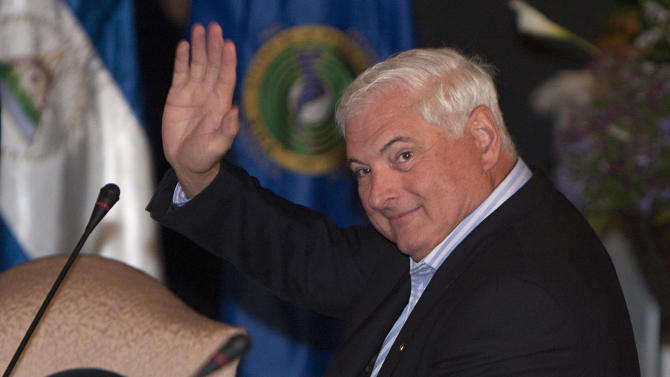 Panama's President Ricardo Martinelli waves to journalists as he attends a presidential summit with Central American leaders in Antigua, Guatemala, Saturday March 24, 2012. Presidents from Central America are meeting ahead of the Summit of the Americas in Cartagena, Colombia in April. (AP Photo/Moises Castillo)