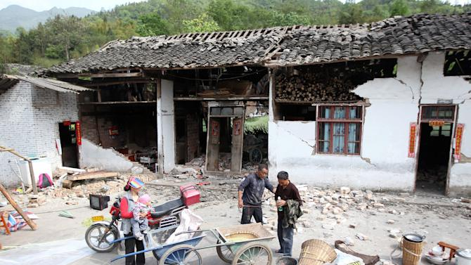 In this photo released by China's Xinhua news agency, residents stand outside their house damaged by an earthquake in Longmen Township, Lushan County, Ya'an City of southwest China's Sichuan Province, Saturday, April 20, 2013. The powerful earthquake struck the steep hills of Sichuan province Saturday, nearly five years after a devastating quake wreaked widespread damage across the region. (AP Photo/Xinhua, Zhang Xiaoli) NO SALES