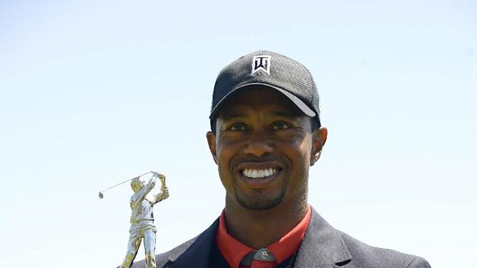 Tiger Woods holds the championship trophy after winning the Arnold Palmer Invitational golf tournament in Orlando, Fla., Monday, March 25, 2013. Woods finished 13-under-par. (AP Photo/Phelan M. Ebenhack)