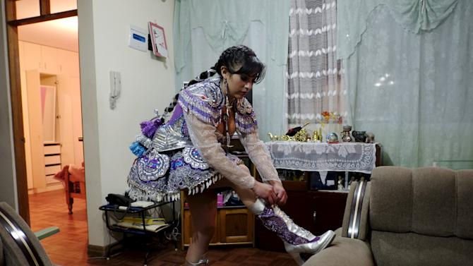 Alicia Vargas, 23, a performer from the Urus Diablada group, tied the laces of her boots before a practice ahead of Carnival in Oruro