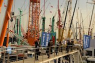 Visitors look at construction machinery at the Bauma China 2012 International Trade Fair in Shanghai on November 28, 2012. Foreign direct investment in China declined for the first time in three years in 2012, official data shows, amid economic turmoil in developed markets and a slowdown at home