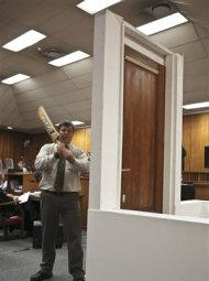 A policeman demonstrates the effect of hitting a bathroom door with a cricket bat during the trial of South African Paralympic athlete Oscar Pistorius in the North Gauteng High Court in Pretoria, March 12, 2014. REUTERS/Alexander Joe/Pool