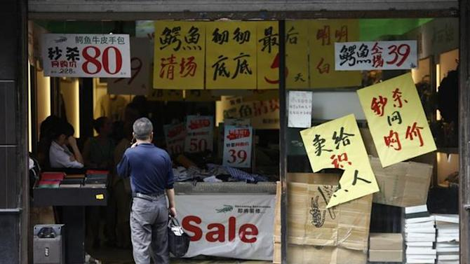 A man looks at sale advertisements outside a shop in Shanghai September 9, 2013. REUTERS/Aly Song