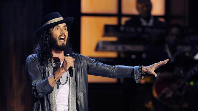"""FILE - In this Nov. 3, 2012 file photo, comedian Russell Brand performs at """"Eddie Murphy: One Night Only,"""" a celebration of Murphy's career, at the Saban Theater in Beverly Hills, Calif. Brand has a deal with Atria Books for a series called """"Russell Brand's Trickster Tales,"""" retellings of classic fairy tales. The publisher announced Wednesday, April 2, 2014, that the first of three planned books, """"The Pied Piper of Hamelin,"""" will be out Nov. 11. The next two books will arrive in 2015 and 2016. (Photo by Chris Pizzello/Invision/AP, File)"""