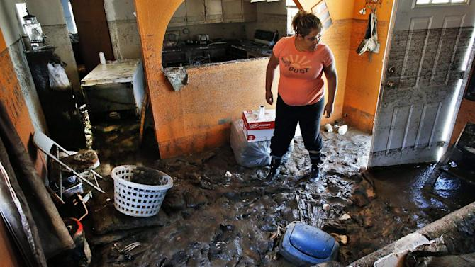 In this Sept. 24, 2013 photo, immigrant Rosi Derma views the flood damage inside her home, which was declared uninhabitable due to permanent damage, at a trailer park in Evans, Colo. The majority of the residents in the trailer park are immigrants who didn't have flood insurance, and because some are not citizens or legal residents, they can't get government help. (AP Photo/Brennan Linsley)