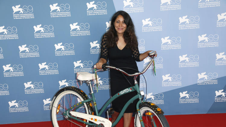 Director Haifaa Al Mansour poses with a bicycle, which is central to the story, during the photo call of the movie 'Wadjda' at the 69th edition of the Venice Film Festival in Venice, Italy, Friday, Aug. 31, 2012. (AP Photo/Joel Ryan)
