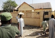 Passersby survey a partially burnt police station in the northern Nigerian city of Kano on January 25. A spokesman for the Boko Haram Islamist group on Saturday rejected a call by Nigeria's president for talks and threatened fresh attacks if captured members of its group were not freed