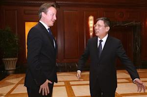 Shanghai Mayor Yang Xiong directs British Prime Minister David Cameron to the meeting venue in Shanghai