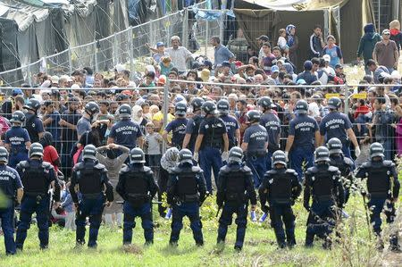 Hungarian riot police stand guard in front of migrant reception centre in Roszke