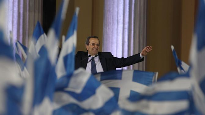 Greece's conservative leader of New Democracy party, Antonis Samaras waves to his party members at the Zappeio conference hall in Athens, Thursday, May 3, 2012. Samaras who joined the majority Socialists in a coalition for the past six months, is leading in opinion polls but is facing a strong challenge from rightist splinter parties and a fascist party that have campaigned heavily on illegal immigration in the crisis-hit country. (AP Photo/Thanassis Stavrakis)
