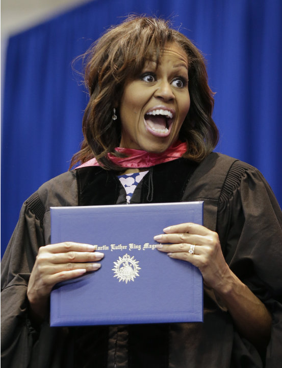 First lady Michelle Obama jokes with a student as she hands out diplomas during the graduation ceremony for Martin Luther King, Jr. Academic Magnet High School on Saturday, May 18, 2013, in Nashville,