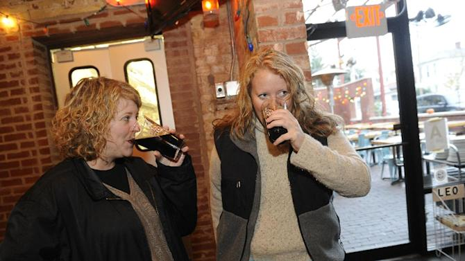 Sara Havens (from left) and Kiley Romanoff, of Louisville, drink Anderson Valley Bourbon Barrel Stout, aged in Wild Turkey Bourbon barrels during the Louisville first pour on Wednesday, Nov. 7, 2012 at the The Silver Dollar in Louisville, KY. (Photo by Joe Imel/Invision for Wild Turkey/AP Images)