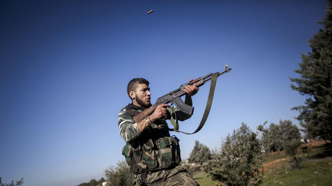In this Saturday, Dec. 15, 2012 photo, a Free Syrian Army fighter aims his weapon during heavy clashes with government forces at a military academy besieged by the rebels north of Aleppo, Syria. Free Syrian Army fighters took control over the military academy after battling government forces for several hours. (AP Photo/Narciso Contreras)