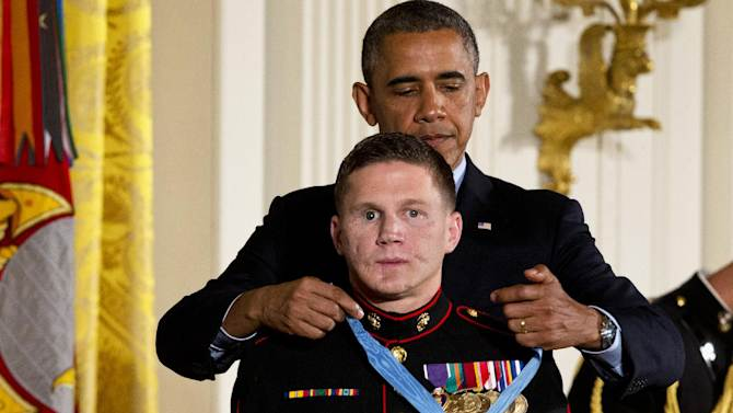 """President Barack Obama awards retired Marine Cpl. William """"Kyle"""" Carpenter, the Medal of Honor for conspicuous gallantry, Thursday, June 19, 2014, during a ceremony in the East Room of the White House in Washington. Carpenter received the Medal of Honor for his courageous actions while serving as an Automatic Rifleman in Helmand Province, Afghanistan. (AP Photo/Jacquelyn Martin)"""