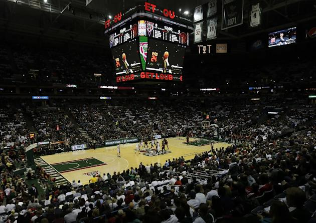 The Milwaukee Bucks and Toronto Raptors tip off during the first half of an NBA basketball game Saturday, Nov. 2, 2013, in Milwaukee. The game is being played on the Bucks old floor after their new fl