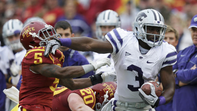 Kansas State wide receiver Chris Harper, right, tries to break a tackle by Iowa State defensive back Jeremy Reeves (5) and linebacker Jake Knott (20) during the first half of an NCAA college football game, Saturday, Oct. 13, 2012, in Ames, Iowa. (AP Photo/Charlie Neibergall)