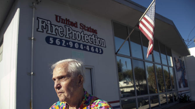 Business owner Dean Wright, 82, pauses outside his neighbor's family-owned business, United States Fire Protection Services, in Downey, Calif. Thursday, Oct. 25, 2012. A gunman killed three people and injured two, including a 13-year-old boy, Wednesday in two separate attacks on a family at their business, United States Fire Protection Services and nearby residence. Police say the five family members who were shot had been targeted by the gunman.  (AP Photo/Damian Dovarganes)