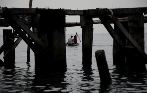 Fishermen paddle their boat in the Philippines