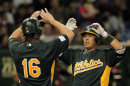 Oakland Athletics' Kurt Suzuki celebrates with teammate Alex Liddi, after two-run home run in the against Japan's Yomiuri Giants in the 7th inning of their exhibition game at Tokyo Dome, Sunday, March 25, 2012. The Athletics will meet the Seattle Mariners in their two season-opening games of the Major League Baseball in Japan, at Tokyo Dome from Wednesday.(AP Photo/Itsuo Inouye)