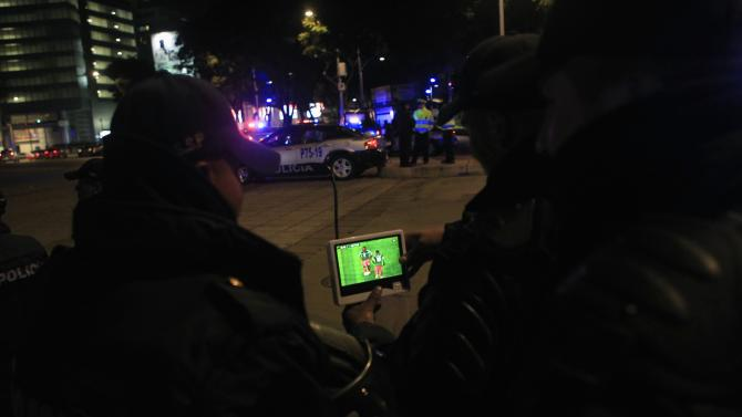 Policemen watch on television the 2014 World Cup intercontinental playoff second leg soccer match between Mexico and New Zealand, in Mexico City