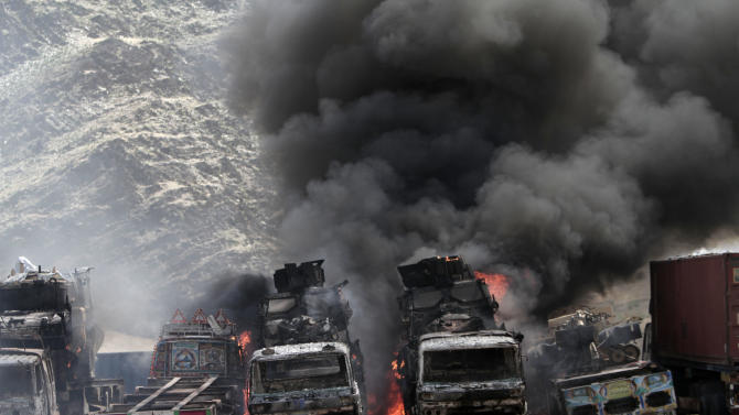 Smoke rises from NATO supply trucks following an attack by militants in the Torkham area near the Pakistan--Afghanistan border in Jalalabad province east of Kabul, Afghanistan, Monday, Sept 2, 2013. The Taliban claimed responsibility for the strike on a U.S. base in Afghanistan near the border with Pakistan on Monday, setting off bombs, torching vehicles and shutting down a key road used by NATO supply trucks, officials said. Several people -- apparently all attacking insurgents -- were killed. (AP Photo/Rahmat Gul)