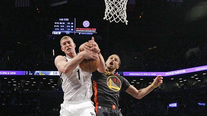 Golden State Warriors guard Stephen Curry (30) tries to strip a rebound from Brooklyn Nets center Mason Plumlee (1) in the first half of an NBA basketball game at the Barclays Center, Monday, March 2, 2015, in New York. The Nets won 110-108. (AP Photo/Kathy Willens)