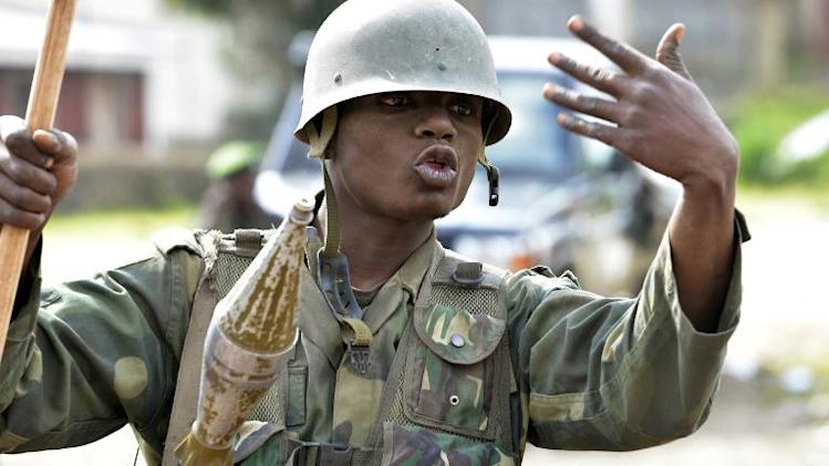 A FARDC governmental soldiers gestures as he patrol on November 1, 2013 in the city of Bunagana, near the border with Uganda