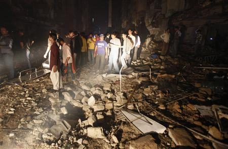 Residents and rescue workers gather at the site of a bomb blast in a residential area in Karachi