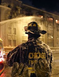 <p>               The frozen ice covered pair of gloves belonging to a Chicago firefighter stand on a railing behind him in single digit temperatures during a five-alarm blaze in a warehouse on the city's South Side, Bridgeport neighborhood rages Wednesday, Jan. 23, 2013, in Chicago. (AP Photo/Charles Rex Arbogast)