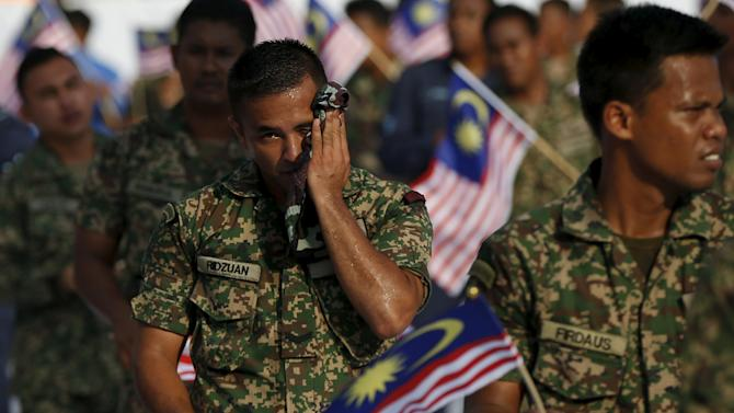 A member of the military wipes his face during rehearsals for Independence Day, or Merdeka Day, in Kuala Lumpur, Malaysia