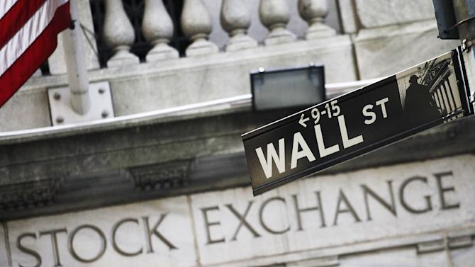 FILE - This July 16, 2013 file photo shows a street sign for Wall Street outside the New York Stock Exchange in New York. U.S. stock futures are steady Wednesday, May 28, 2014, with the market market hovering at record levels. (AP Photo/Mark Lennihan, File)