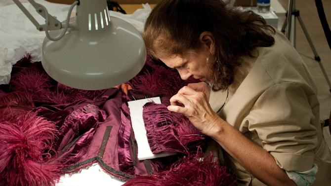 "In this undated photo provided by the Harry Ransom Center, conservator Cara Varnell works on the burgundy ball gown from ""Gone With The Wind."" Varnell determined that some feathers were original and some were replacements. The ball gown as well as the iconic green curtain dress from the 1939 film were saved from deterioration by a $30,000 conservation effort by the Harry Ransom Center at the University of Texas, and are on display for the first time in nearly 30 years at London's Victoria and Albert Museum as part of a Hollywood costume exhibit. (AP Photo/Harry Ransom Center)"