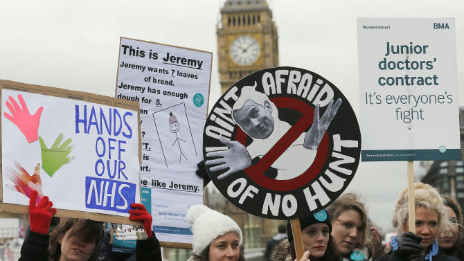 Junior National Health Service (NHS) doctors wave placards referring to British Conservative Party Secretary of State for Health, Jeremy Hunt, during a protest outside St Thomas Hospital in London, Wednesday, Feb. 10, 2016, backdropped by the Houses of Parliament and Big Ben's clock tower.  Thousands of junior doctors have walked off the job in England in a dispute over pay and working conditions.(AP Photo/Frank Augstein)