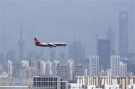 A Shanghai Airlines' passenger airliner flies towards Hongqiao Airport in Shanghai in this August 6, 2010 file photo. REUTERS/Aly Song/Files