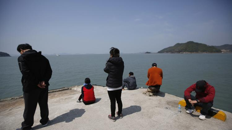 Family members of missing passengers who were on the South Korean passenger ferry Sewol which sank in the sea off Jindo, look towards the sea at a port in Jindo