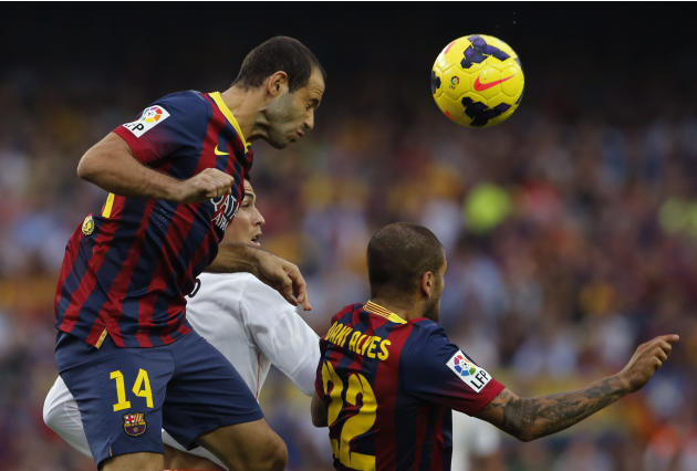 Barcelona's Javier Mascherano from Argentina, left, and Daniel Alves from Brazil, right, jumps for the ball with Real Madrid's Cristiano Ronaldo from Portugal during a Spanish La Liga soccer match bet