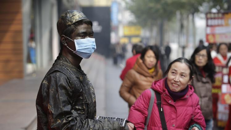 A woman looks up at an artist dressed up as a bronze statue wearing a face mask along a street in Wuhan