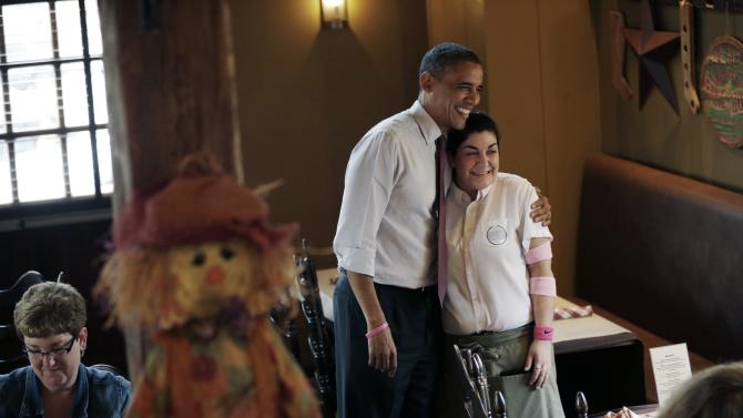 President Barack Obama poses for a photograph with waitress as he greets local patrons during an unscheduled visit to the Common Man Merrimack restaurant, Saturday, Oct. 27, 2012 in Merrimack, N.H. (AP Photo/Pablo Martinez Monsivais)