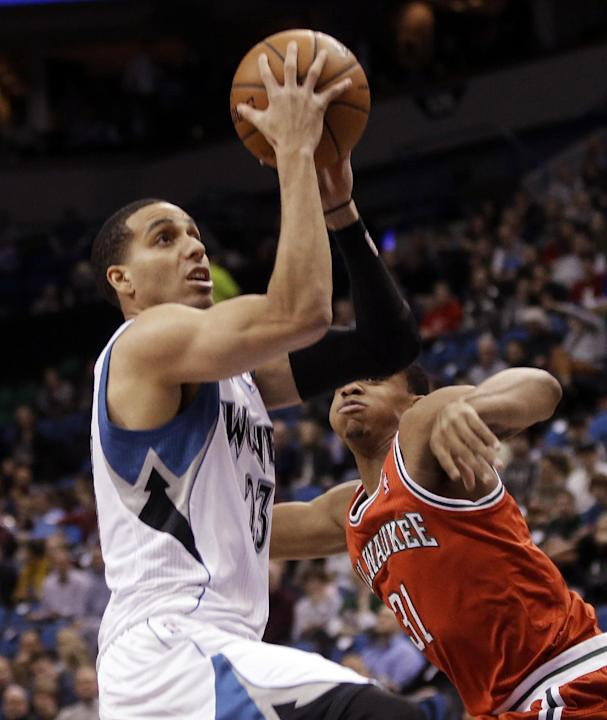 Minnesota Timberwolves' Kevin Martin lays up as Milwaukee Bucks' John Henson watches in the first quarter of an NBA basketball game, Tuesday, March 11, 2014, in Minneapolis