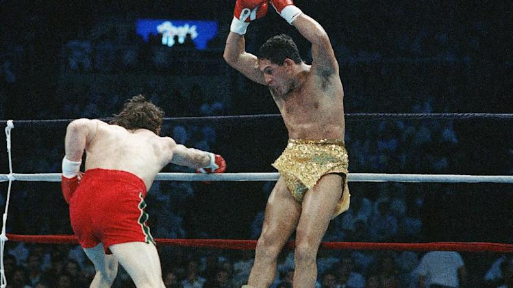"FILE - In this March 7, 1989 file photo, Hector ""Macho"" Camacho jumps out of the way of a punch thrown by Ray Mancini during the third round of their WBO Junior Welterweight Championship boxing match in Reno, Nev. Camacho, a boxer known for skill and flamboyance in the ring, as well as for a messy personal life and run-ins with the police, has died, Saturday, Nov. 24, 2012, after being taken off life support. He was 50.  (AP Photo/Eric Risberg, File)"