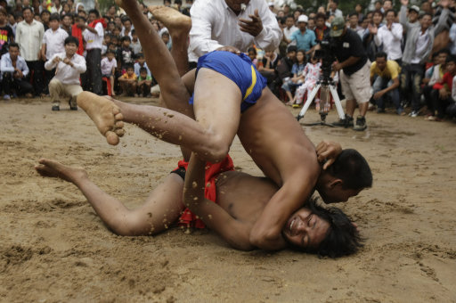 Cambodian men compete in a traditional wrestling style at Preah Vihear Sour pagoda on Tuesday, Sept. 27, 2011, in Kandal province, some 40 kilometers (25 miles) northeast of Phnom Penh, Cambodia. Residents of the village on Tuesday held an annual water buffalo race to mark the end of a traditional celebration known as the Festival for the Dead in Cambodia. (AP Photo/Heng Sinith)
